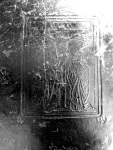 High contrast detail of the blind panel stamp from the front board of TypFP.B01HF, a Crucifixion scene with Mary and St. John kneeling.