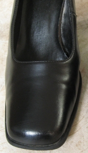The shoe with the cheap blacking. A shine has now appeared after buffing with a polishing brush.