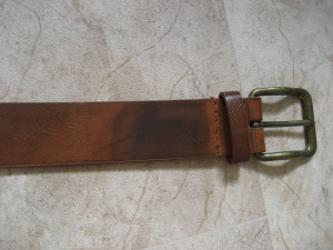 Testing the blacking on a brown leather belt. The end near the buckle has had the oil and vinegar blacking applied, and is now a darker colour.