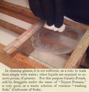 Cleaning a glass plate with sodium carbonate is best done with a wooden vice to securely hold the glass.
