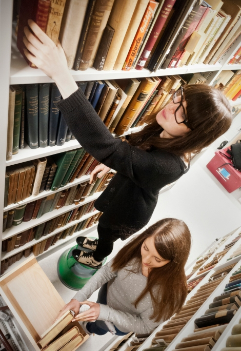 Two of the original Lighting the Past members, Cecilia Vinesse, and Emma Collins, retrieving books in the stacks.