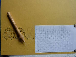 The pattern being pricked out onto card