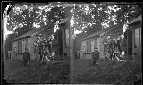 Stereoview of Lord Kinnaird (holding lens cap), likely with Lady Kinnaird (behind camera) and other photographers and darkroom technicians posing with an 1853 Ottewill folding camera in front of their dark room at Rossie Priory.