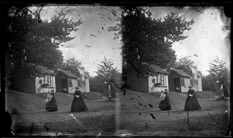 Stereoview of two women, one holding a baby [PHtempCB-A-16]. Unvarnished image shows extensive scratches. As the two women here are both slightly out of focus the photographer likely was not planning on using the image. Happily, the plate was not destroyed as the Rossie Priory darkroom and skylight studio can be seen clearly behind them.