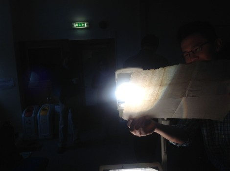 A student uses back-lighting from an old transparency projector to identify watermarks from a loose leaf of paper from Harris's own collection