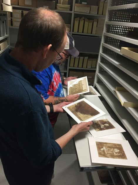 Members of The Calotype Society looking at some mounted early prints from the collection.